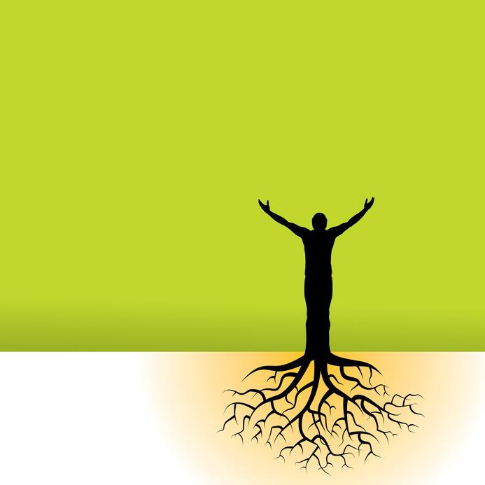 Wir sehen ein Sinnbild: Ein schwarzer Mann steht mit erhobenen Händen vor einer grünen Fläche. Unter seinen Füßen reichen viele Wurzeln in den Boden.