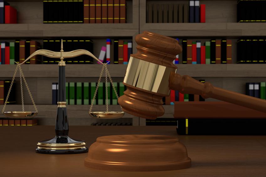 Ein ausgeglichene Waage und der Gerichtshammer stehen vor einem Bücherregal.