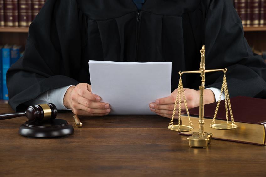 Ein Richter liest in seinem Skript. Eine Waage, ein Stift und sein Hammer liegen vor ihm.