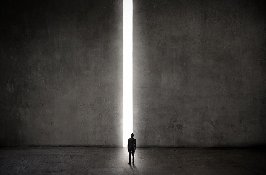 Ein Mann steht vor einer Übergroßen Tür, welche ein Spalt weit geöffnet ist.