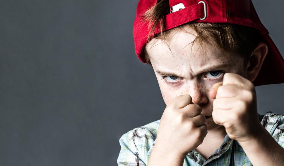 Ein Junge steht mit geballten Feusten vor dir.