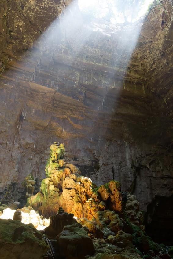 Im Berginneren fällt ein Lichtstrahl auf einen grün bewachsenen Stein.