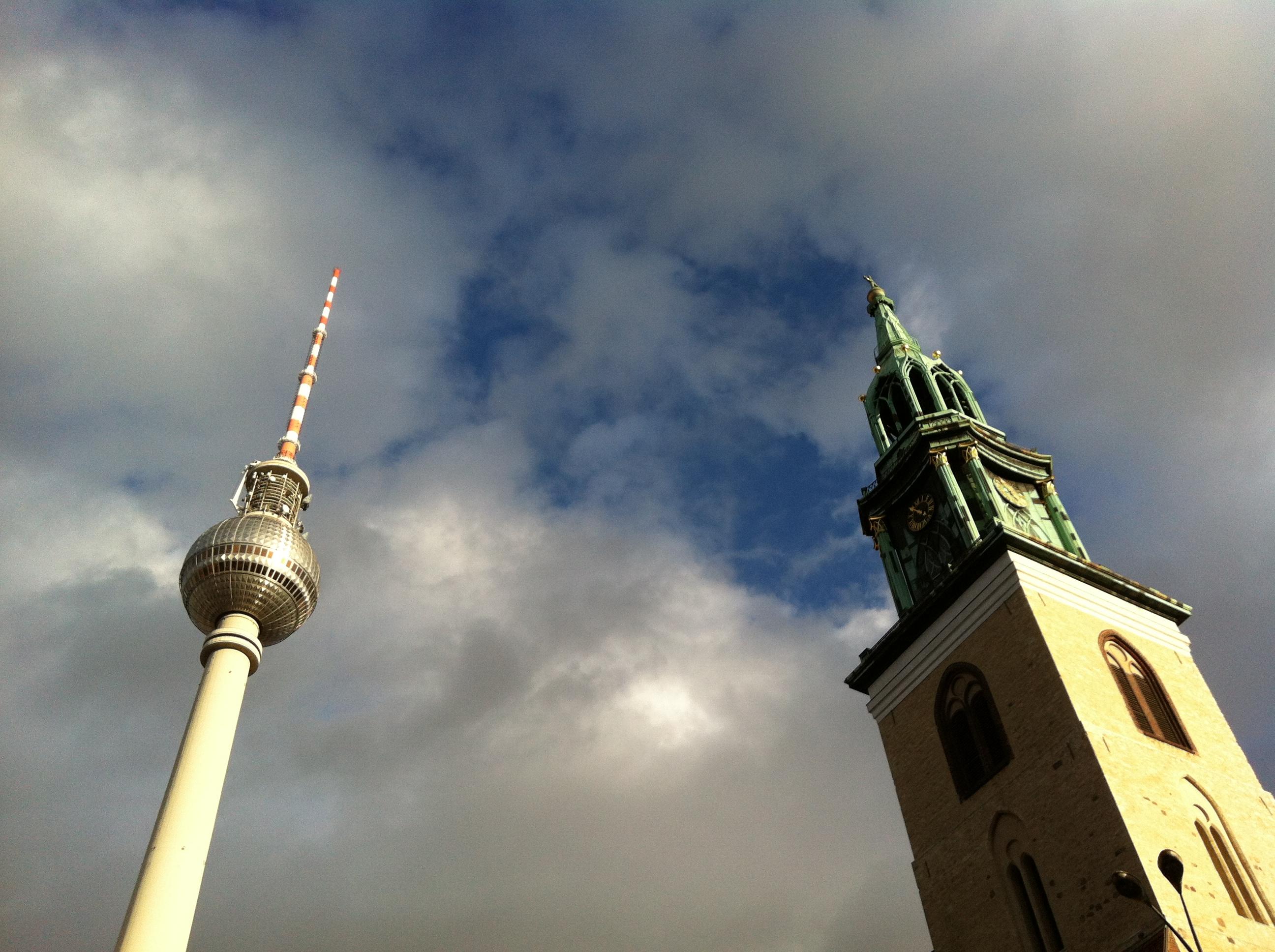 In Berlin ragen der Fernsehturm und ein Kirchturm in den Himmel.