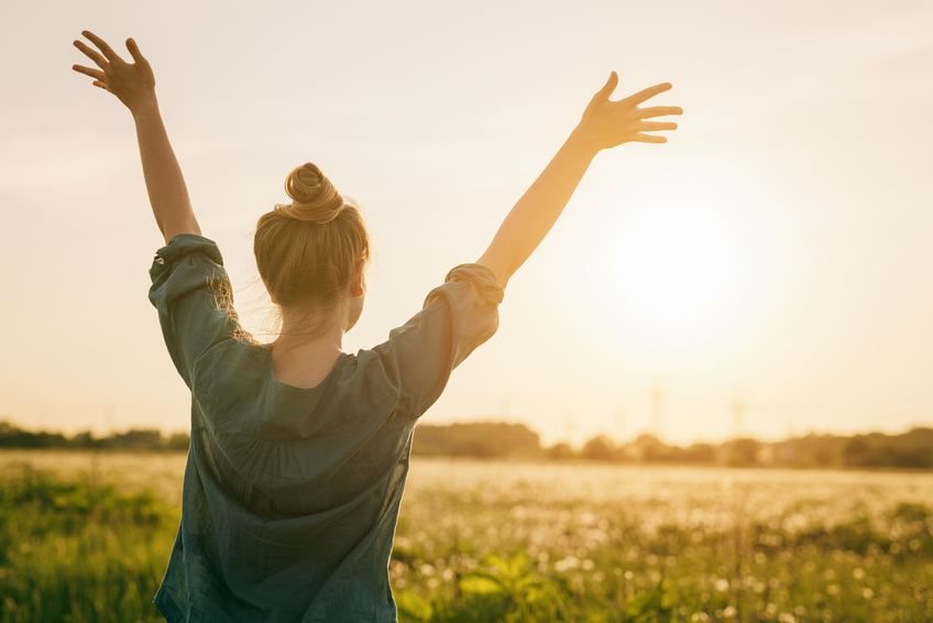 Eine Frau schaut der Sonne entgegen und bebt sorglos ihre Arme.