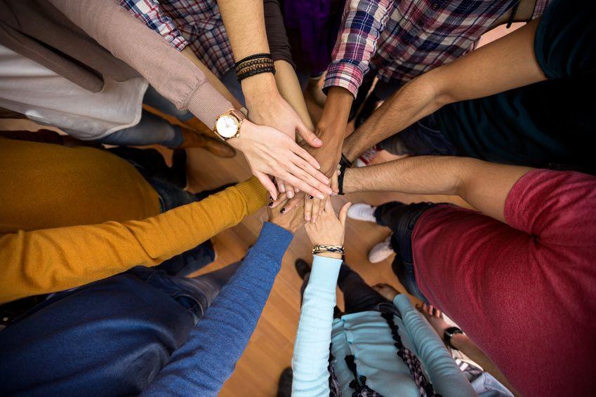 Viele Personen haben imKreis stehend ihre Hände in der Mitte übereinander gelegt.