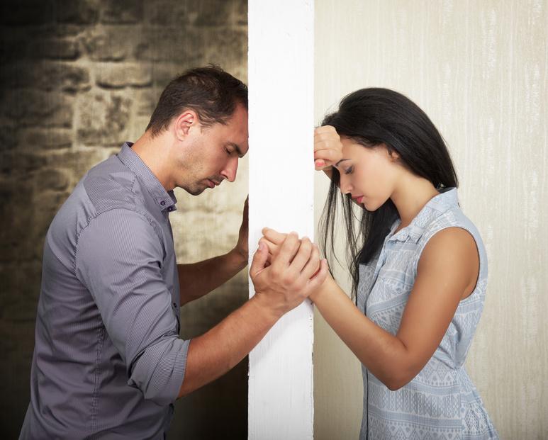 Frau und Mann stehen sich verzweifelt gegenüber. Eine Wand trennt sie voneinander. Vor der Wand hält seine rechte Hand ihre Linke.