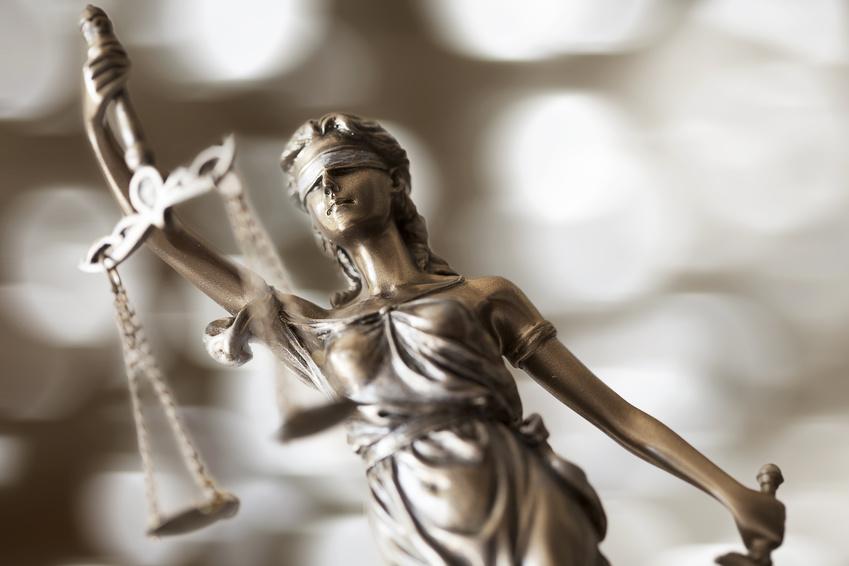Justizia hält mit verbundenen Augen in der Hand eine Waage.