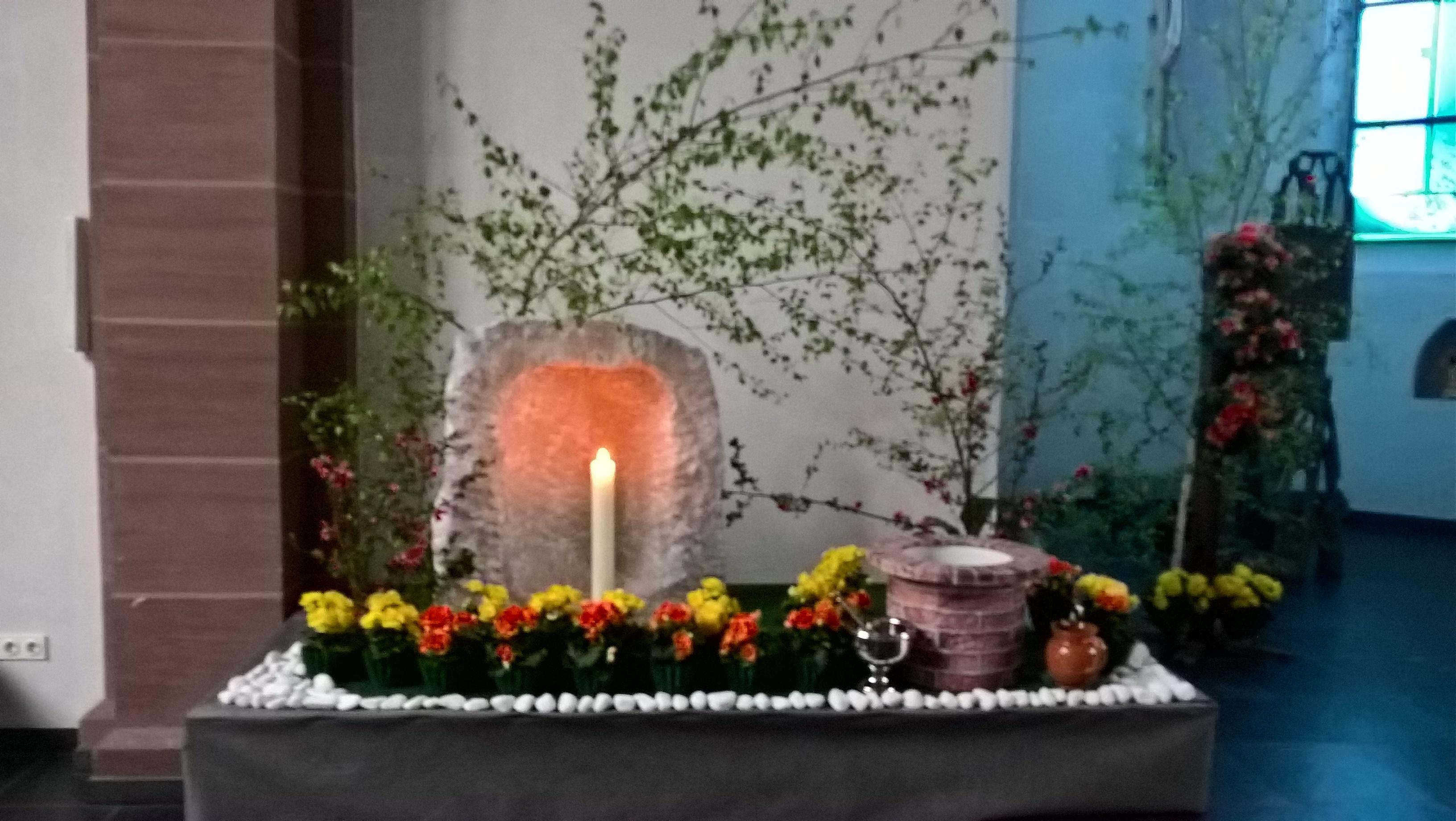Vor einer hellen Holle aus Stein brennt eine Kerze!