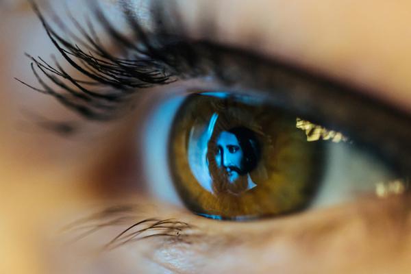 Auf der Pupille eines Auges ist das Gesicht Jesus zu erkennen.