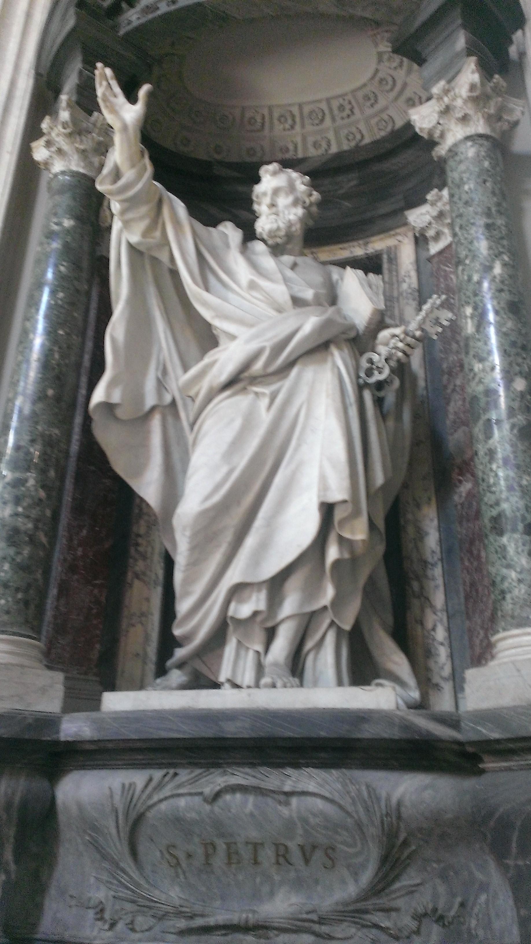 Petrus streckt seine rechte Hand aus und hält unterm linken Arm die Heilige Schrift und in der linken Hand einen Schlüssel.