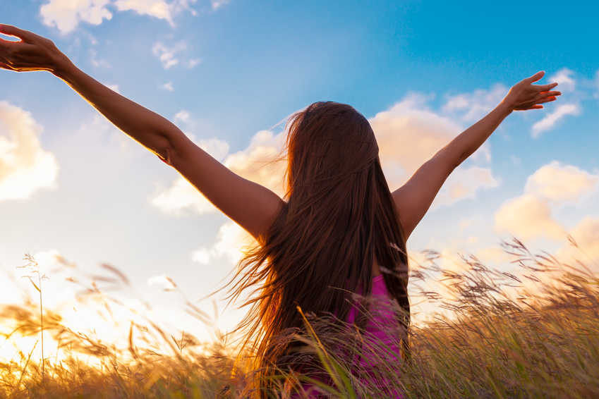 Eine Frau breitet die Arme aus und schaut zum Himmel.