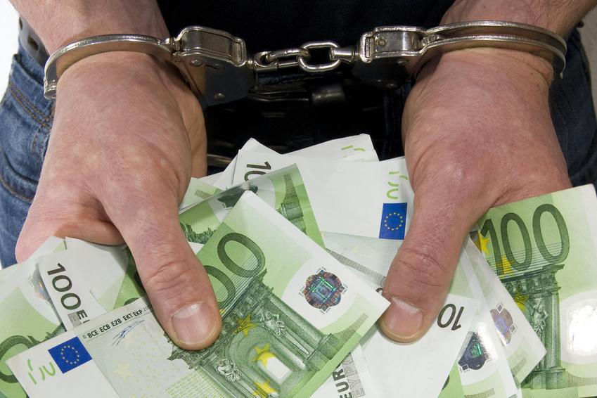 Mit Handschellen gefesselte Hände halten viele Geldscheine.