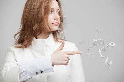 Eine Frau zeigt mit ihrer rechten Hand eine Pistole aus der sie Buchstaben schießt.