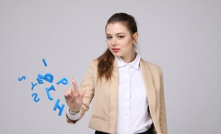 Eine Frau weißt bedacht  mit ihrem rechten Zeigefinger nach oben, wor sie mit Buchstaben Wörter gestalten kann.