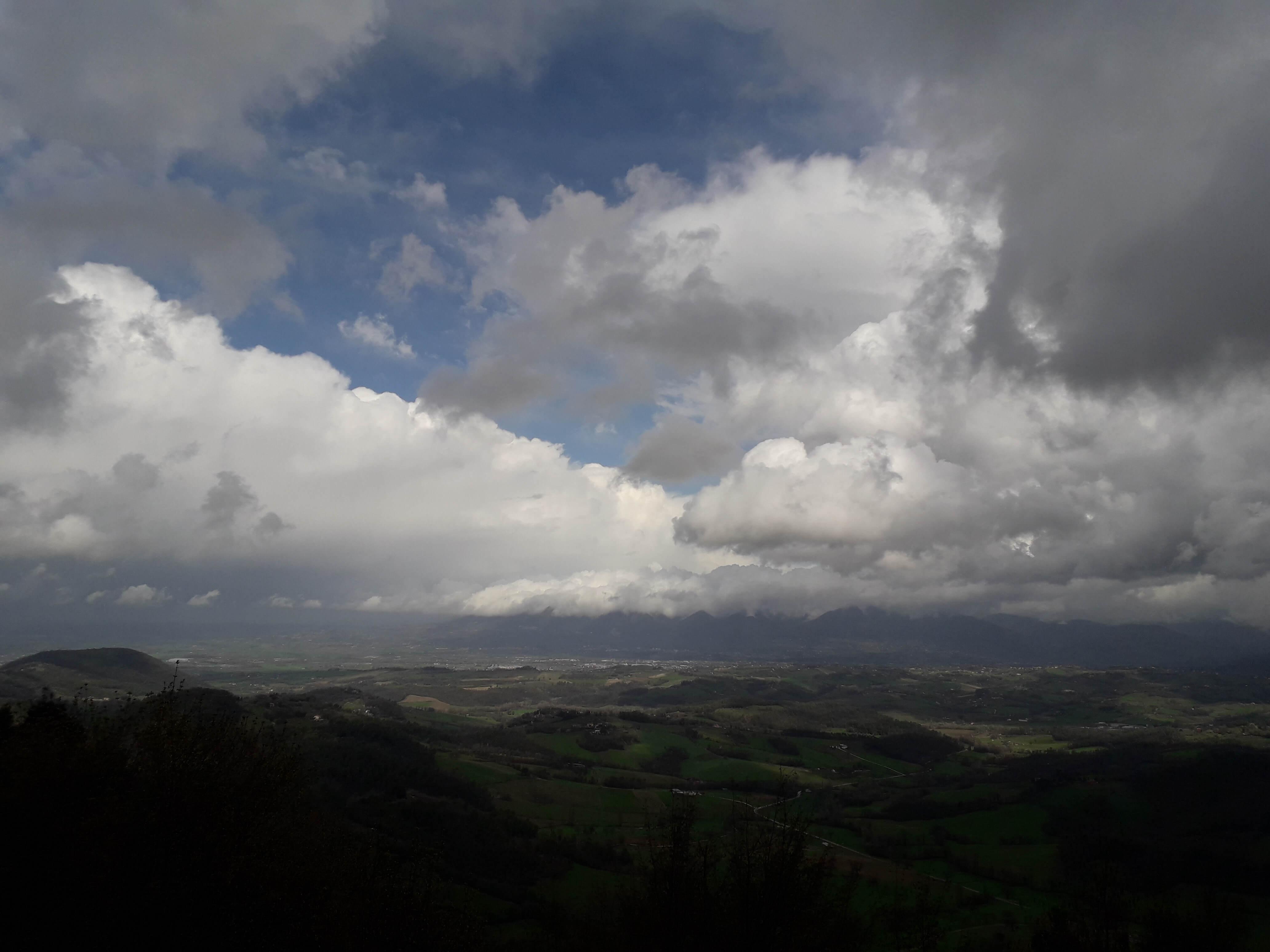 Bergzüge im Vorder- und Hintergrund schließen ein mit dunklen Wolken behangenes Tal ein.