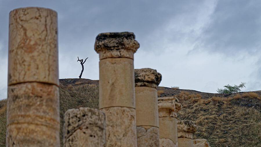 Hinter verwitterten Säulen erscheinen am Horizont neue Gewächse. Ein junger Spross gleicht den Umrissen eines Menschen, der seine Arme zum Himmel erhoben hat.
